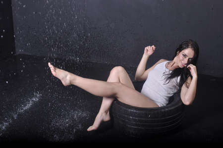 Beautiful athletic girl sitting on rubber wheels smiling Stock Photo