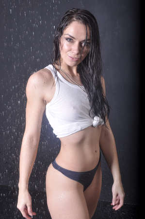 Sport brunette in a wet t-shirt on a black background