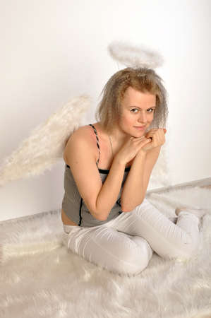 Angel girl sits on a white carpet