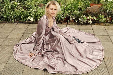 Beautiful girl in a dress sitting in a garden resting