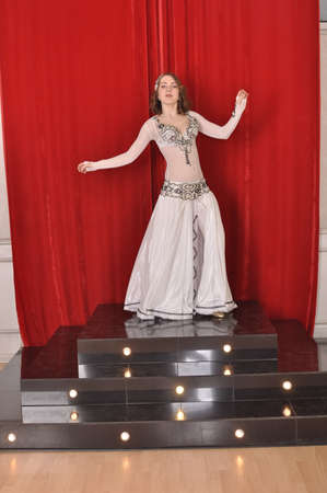 Girl in white oriental costume dancing belly dance on red background