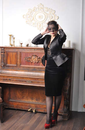 Girl in black mask standing at piano