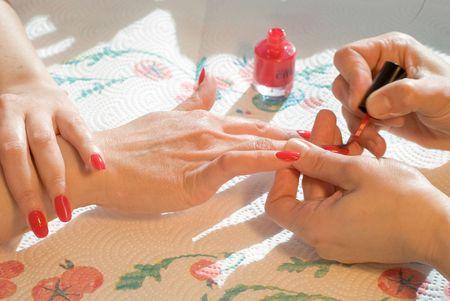 woman applying red nail polish photo