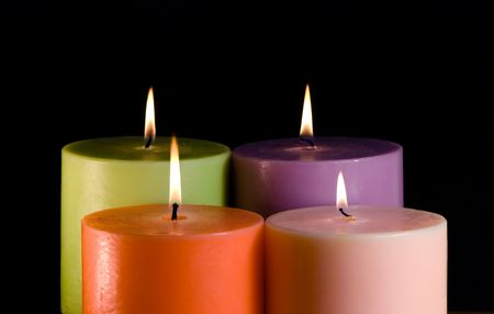 nearness: four candles isolated on a black