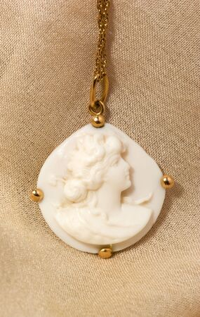 cameo: close-up of Antique Cameo isolated on beige fabric
