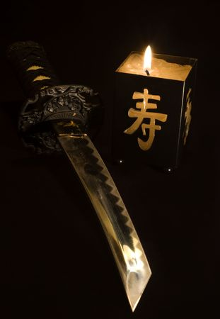 small japanese sword and candlestick isolated on black background Stockfoto