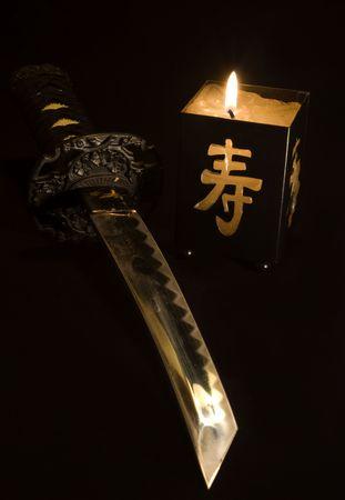 katana: Kleine Japanse zwaard en candlestick geïsoleerd tegen zwarte achtergrond