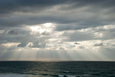 Rays of light shining through dark clouds photo