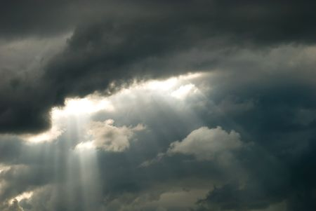 Rays of light shining through dark clouds Stockfoto