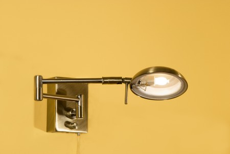 sconce: decorative glowing metallic sconce on a wall