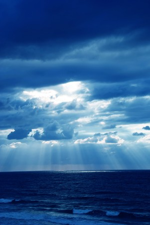 Rays of light shining through dark clouds photo