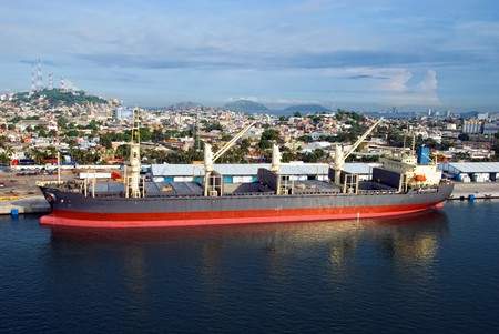 loading cargo: Large cargo ship in a harbor of Mazatlan, Mexico Stock Photo