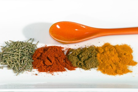 spices and ceramic spoon on a white plate photo