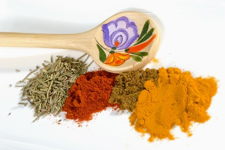 spices and wooden spoon on a white plate photo