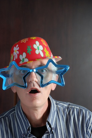 adult man with toy glasses and hat photo