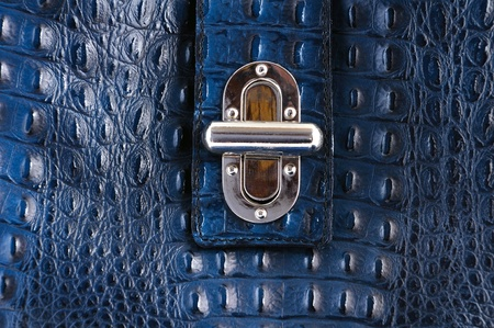 blue leather bag with lock, closeup photo
