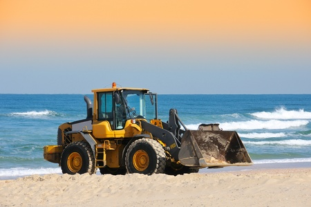 truckload: bulldozer working on a beach Stock Photo