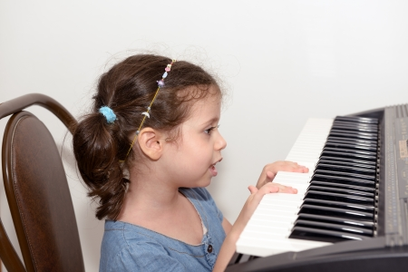 Little girl plays electric piano Stock Photo - 14325423