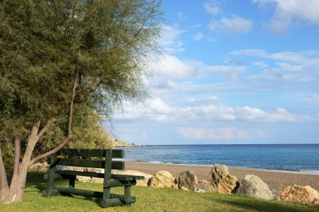 alone bench on the beach of mediterranean sea, Rhodes, Greece photo