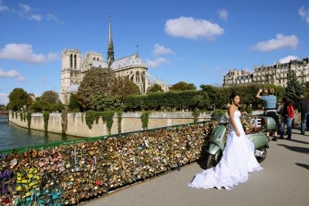 amorousness: PARIS, FRANCE - SEPTEMBER, 26:The bride posing for photografer on the love locks bridge on September 26, 2012 in Paris.  Editorial