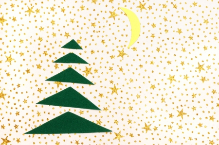 Paper Christmas tree and moon on an ornamental background photo