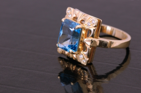 gold ring with big blue gem and smaller diamonds photo
