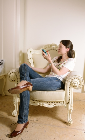 young woman sitting on  armchair photo