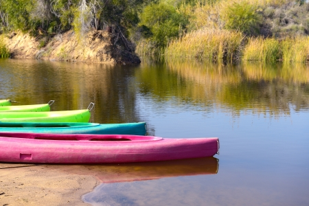 several  colored canoes on a beach of tranquil lake photo