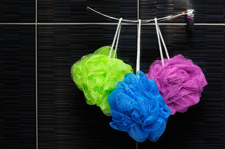 three colorful shower scrubbers hanging in a bathroom  photo