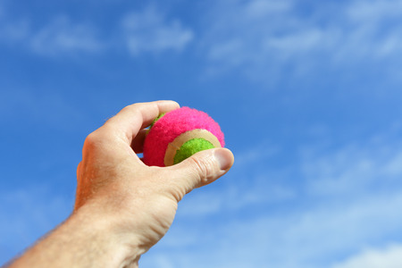 grasp: Player gripping a  tennis ball over blue sky Stock Photo