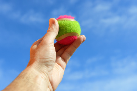 Player gripping a  tennis ball over blue sky Stock Photo - 27737641