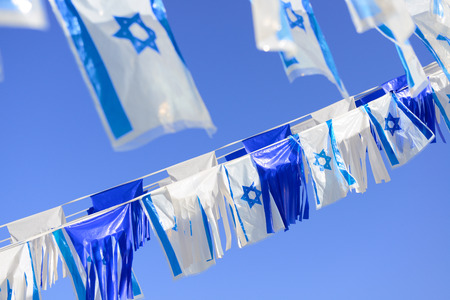 Israel flags in a chain over blue sky.  photo