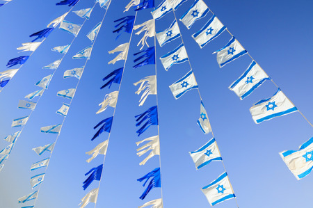 Israel flags in a chain over blue sky. Independence Day.