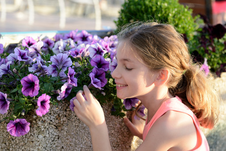 Little girl smelling flowers on the city street. Stock Photo