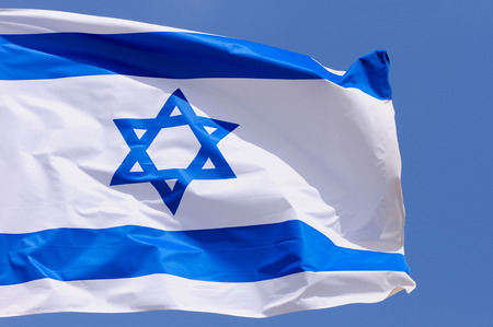 big flag of Israel over blue sky photo