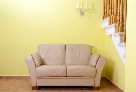 yellow  interior with a beige sofa and staircase photo