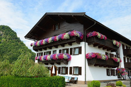 house with lot of petunia flowers on balcony