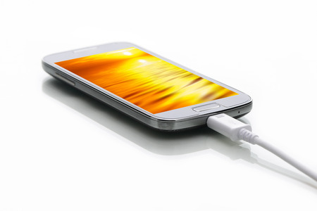 modern smartphone with screensaver and usb cable on a white background photo