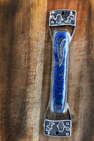 mezuzah: blue glass handmade mezuzah on a wooden surface