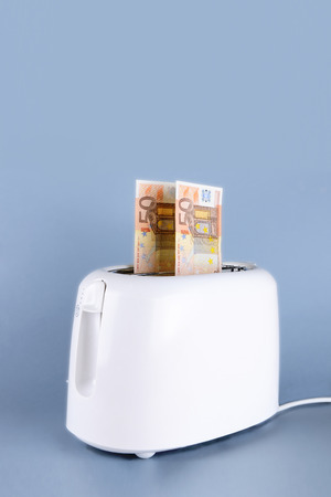 euro in the toaster over gray background photo