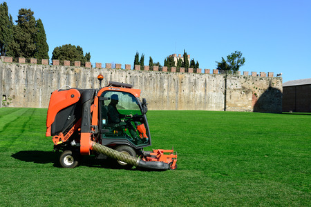 gardening equipment: PISA,ITALY-MARCH 06,2015: Lawn mower cuts a grasson the Square of Miracles in Pisa. Pisa is a city in Tuscany, Central Italy and it is famous with Leaning Tower.