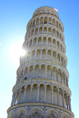 Leaning tower in Pisa with sun rays over blue sky photo