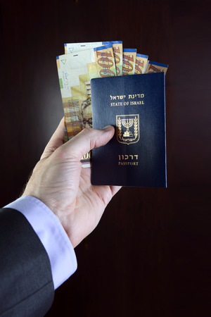 israel passport: male hand holding a passport with New Sheqalym  banknotes of Israel. Stock Photo