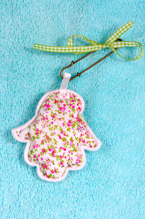hebrew script: Hamsa hand amulet made from textile with floral pattern