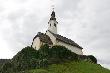 Oude kerk over sombere hemel. Resort Maria Worth. Oostenrijk.