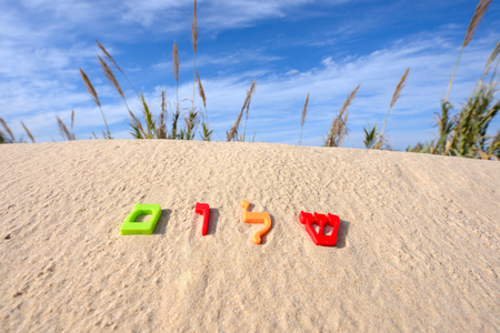 hebrew: Plastic characters of Hebrew alphabet on a sand. Hebrew word Shalom meaning peace hello goodbye.