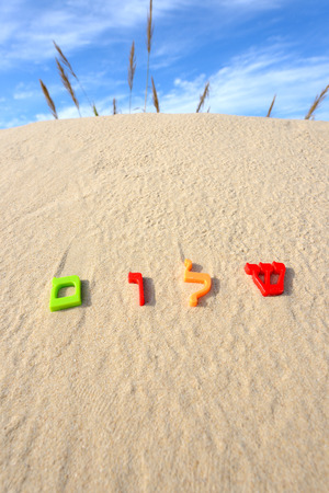 shalom: Plastic characters of Hebrew alphabet on a sand. Hebrew word Shalom meaning peace hello goodbye.