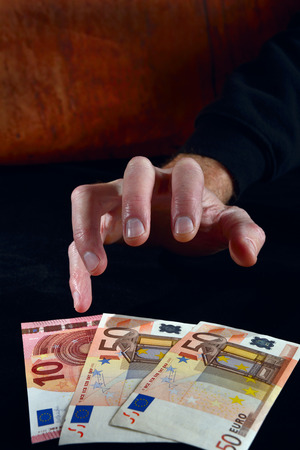 avarice: Greedy hand reaches for euro money. Image in low key.