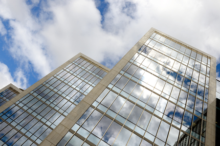 superstructure: DUBLIN, IRELAND- JULY 28, 2016: Modern office buildings over cloudy sky with reflection in windows.