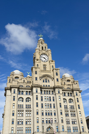 Liverpool city centre - Three Graces, buildings on Liverpools waterfront, UK over cloudy sky.